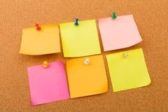 Tablero con las notas en blanco coloreadas fijadas - imagen del corcho imagenes de archivo