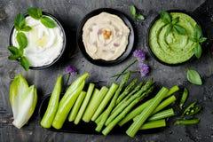 Tablero crudo del bocado de las verduras verdes con las diversas inmersiones Salsa o labneh del yogur, hummus, hummus de la hierb fotografía de archivo