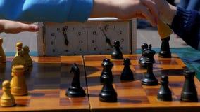 Tablero de ajedrez con el reloj y las figuras del ajedrez Competencias en inspectores entre niños almacen de video