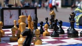 Tablero de ajedrez con el reloj y las figuras del ajedrez Competencias en inspectores entre niños metrajes