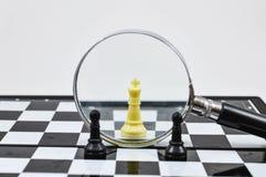 Tablero de ajedrez con la lupa Imagenes de archivo