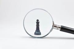 Tablero de ajedrez con la lupa Foto de archivo libre de regalías