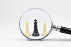 Tablero de ajedrez con la lupa Fotografía de archivo libre de regalías