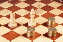 Tablero de ajedrez con las monedas y los pedazos de ajedrez Foto de archivo libre de regalías
