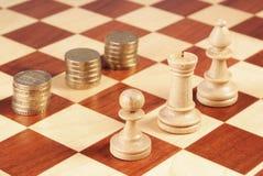 Tablero de ajedrez con las monedas y los pedazos de ajedrez Imágenes de archivo libres de regalías