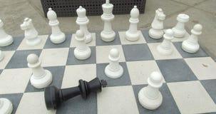 Tablero de ajedrez gigante con el rey negro caido almacen de video