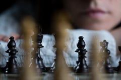 Tablero de ajedrez de observación de la mujer fotografía de archivo