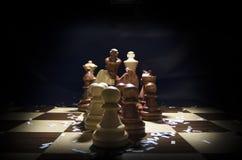 Tablero de ajedrez y pedazos bajo luz Fotos de archivo libres de regalías