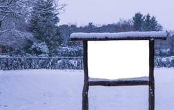 Tablero de anuncio de madera vacío y en blanco cubierto en nieve, estación en el bosque, cartelera del invierno de la publicidad foto de archivo libre de regalías