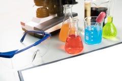 Tablero de la conferencia de la ciencia con el experimento químico en el laboratorio con los cubiletes, microscopio de la escuela fotografía de archivo libre de regalías