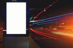 tablero de la información pública en ciudad de la noche con los coches del movimiento en el fondo, mofa clara de la publicidad al imágenes de archivo libres de regalías