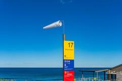 Tablero de la manga de viento y de la información Fuerte viento en la playa Foto de archivo libre de regalías