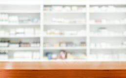 Tablero de la mesa de madera de Brown con la farmacia borrosa Imagen de archivo