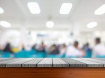 Tablero de la mesa de madera debajo borroso de gente o de pacientes de la imagen en hospital imagen de archivo