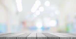 Tablero de la mesa de madera debajo borroso de gente o de pacientes de la imagen en hospital fotografía de archivo