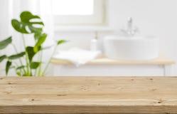 Tablero de la mesa vacío para la exhibición del producto con el fondo borroso del interior del cuarto de baño