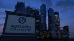 Tablero de la señalización de la calle con el logotipo de China Mobile por la tarde Fondo borroso de los rascacielos del distrito Fotos de archivo libres de regalías