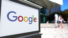 Tablero de la señalización de la calle con el logotipo de Google Centro borroso de la oficina y fondo de la gente que camina Repr almacen de video