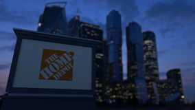 Tablero de la señalización de la calle con el logotipo de Home Depot por la tarde Fondo borroso de los rascacielos del distrito f Imágenes de archivo libres de regalías