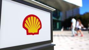 Tablero de la señalización de la calle con el logotipo de Shell Oil Company Centro borroso de la oficina y fondo de la gente que  Imágenes de archivo libres de regalías