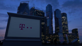 Tablero de la señalización de la calle con el logotipo de T-Mobile por la tarde Fondo borroso de los rascacielos del distrito fin Foto de archivo libre de regalías