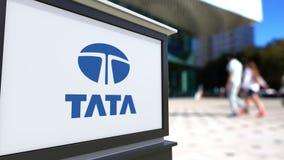 Tablero de la señalización de la calle con el logotipo de Tata Group Centro borroso de la oficina y fondo de la gente que camina  ilustración del vector