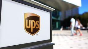 Tablero de la señalización de la calle con el logotipo de United Parcel Service UPS Centro borroso de la oficina y fondo de la ge Imagen de archivo