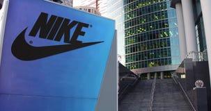 Tablero de la señalización de la calle con la inscripción y el logotipo de Nike Rascacielos moderno del centro de la oficina, fon stock de ilustración