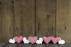 Tablero de madera adornado con los corazones comprobados para una tarjeta de felicitación. Imagen de archivo