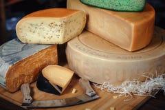 Tablero de madera con diversas clases de sabroso en la tabla con queso verde de la arcón del queso de los cuchillos fotografía de archivo libre de regalías