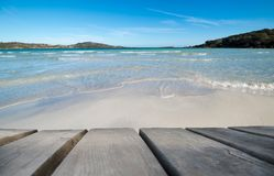 Tablero de madera con la playa hermosa como fondo imagenes de archivo