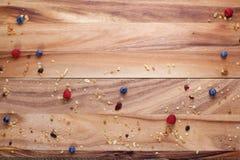 Tablero de madera con las bayas y el Granola dispersados con el espacio del texto Fotografía de archivo
