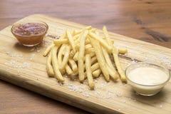 Tablero de madera con las patatas fritas o las patatas fritas fotos de archivo