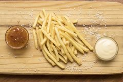 Tablero de madera con las patatas fritas y las salsas imágenes de archivo libres de regalías