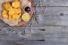 Tablero de madera con las pepitas y las salsas sabrosas de pollo en la tabla Foto de archivo libre de regalías