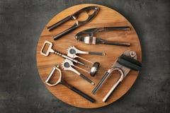 Tablero de madera con los diversos utensilios de la cocina Fotos de archivo