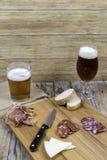 Tablero de madera con los vidrios de la salchicha, del queso y de cerveza Fotografía de archivo libre de regalías