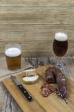 Tablero de madera con una salchicha y los vidrios de cerveza Fotos de archivo libres de regalías