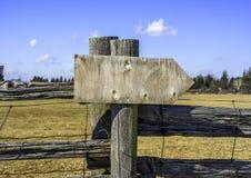 Tablero de madera de la muestra de la flecha en los posts rústicos de la cerca en backgrou al aire libre Imagenes de archivo