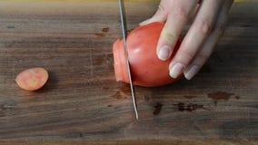 Tablero de madera de la mujer de la mano de la rebanada del cuchillo ecológico rojo rápido del tomate metrajes