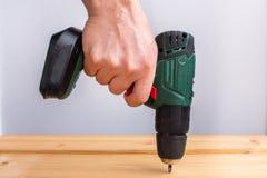 Tablero de madera del taladro y de la perforación de la batería de la tenencia de la mano de los hombres imagen de archivo libre de regalías