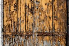 Tablero de madera llevado viejo grunge con la pintura amarilla marrón agrietada y pelada imagen de archivo