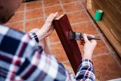Tablero de madera pintado con el cepillo de pintura Renovación casera y concepto de DIY Hombre joven que sostiene los cepillos pi fotografía de archivo libre de regalías