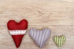Tablero de madera con tres corazones de paño Fotos de archivo libres de regalías