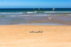 Tablero de resaca en la arena con las personas que practica surf en ondas en la distancia Foto de archivo libre de regalías
