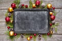 Tablero de tiza clásico de la Navidad y de la composición del Año Nuevo, bolas, juguetes, caramelo, ramas del abeto en fondo de m Imagenes de archivo