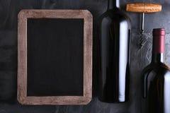 Tablero de tiza y botellas de vino Foto de archivo libre de regalías