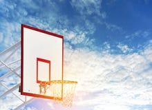 Tablero del baloncesto con la red del aro en la tierra del juego de la bola de la cesta el día soleado con el cielo azul claro y  fotografía de archivo libre de regalías