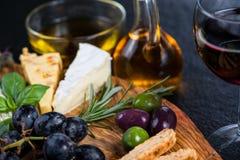 Tablero del estilo de los Tapas con queso, las aceitunas y el vino Fotos de archivo libres de regalías