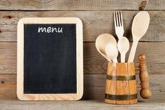 Tablero del menú y cucharas y bifurcación en taza Foto de archivo